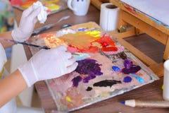 L'artiste expulse peinture des tubes sur la palette pour les couleurs de mélange t Photo libre de droits