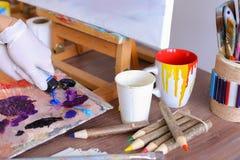 L'artiste expulse peinture des tubes sur la palette pour les couleurs de mélange t Image libre de droits