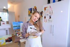 L'artiste Girl Holds Brush à disposition et dessine sur la toile, prend le pH Photos libres de droits