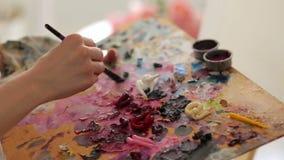 L'artiste mélange la peinture sur la palette à une brosse, plan rapproché banque de vidéos