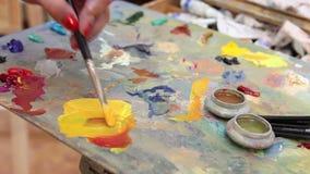 L'artiste mélange la peinture sur la palette, la peinture mélangée par brosse d'art sur la palette, peinture à l'huile de couleur banque de vidéos