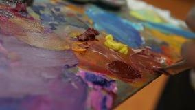 L'artiste mélange la peinture sur la palette, la peinture mélangée par brosse d'art sur la palette, peinture à l'huile de couleur clips vidéos