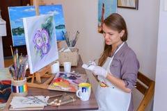 L'artiste mignonne Holds Brush de fille à disposition et tire, boit de la tasse, Photographie stock