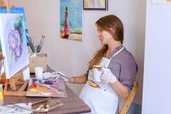 L'artiste mignonne Holds Brush de fille à disposition et tire, boit de la tasse, Photos stock