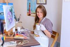 L'artiste mignonne Holds Brush de fille à disposition et tire, boit de la tasse, Photos libres de droits