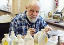 L'artiste peignant les bouteilles en céramique Images libres de droits