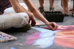 L'artiste peint un tableau avec la craie sur l'asphalte images libres de droits