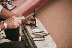 L'artiste supérieur thaïlandais du nord handcraft l'argent de tailleur avec le marteau Photo libre de droits