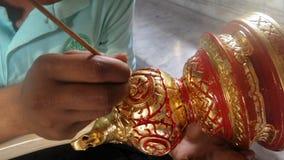L'artiste thaïlandais mettant l'or sur la couleur rouge a peint le bouton découpé en bois Photographie stock