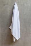 L'asciugamano bianco sta appendendo su un gancio con il muro di cemento in Immagini Stock
