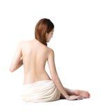 L'asciugamano d'uso della donna asiatica che si siede sul pavimento indietro osserva Fotografia Stock
