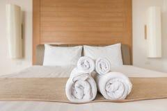 L'asciugamano rotola su un letto dell'hotel Fotografie Stock