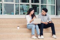 L'asiatico coppia gli studenti o i colleghi che si siedono alle scale ed alla s Fotografie Stock
