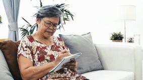 L'asiatico riflette la donna senior che pensa e che scrive qualcosa stock footage