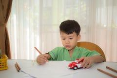 L'Asiatique 3 ans badinent le dessin et jouent le jouet Karl pour détendre après recov Image stock
