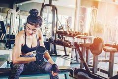 L'Asiatique folâtre la femme faisant des exercices avec des poids d'haltère dans le gymnase photo stock