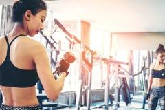 L'Asiatique folâtre la femme faisant des exercices avec des poids d'haltère dans le gymnase Photo libre de droits