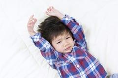 L'Asiatique mignon Little Boy se réveillent sur le lit Avec un visage somnolent Images stock