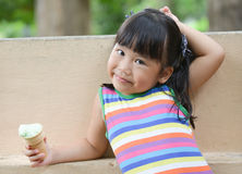 L'Asiatique mignonne de fille aiment manger de la glace images libres de droits