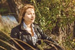 L'Asiatique s'assied à côté d'un arbre Images libres de droits