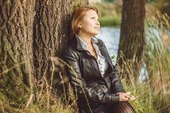 L'Asiatique s'assied à côté d'un arbre Photographie stock
