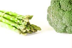 L'asparago ed i broccoli del fondo dell'alimento pongono pianamente il modello mazzo di asparago verde fresco su fondo bianco, vi immagine stock