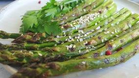 L'asparago ha arrostito le cadute su fondo concreto grigio, movimento lento video d archivio