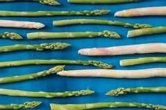 L'asparago verde e bianco fresco spara il modello, su una vista superiore del fondo di legno blu Fotografia Stock
