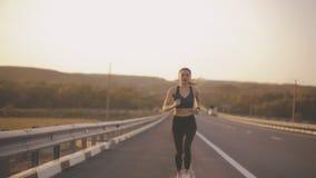 L'aspect caucasien de fille, occupé dans le sport pulsant sur la route, surmonte la fatigue banque de vidéos