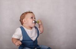 L'aspect européen de bébé mange du gruau d'une cuillère Photographie stock libre de droits
