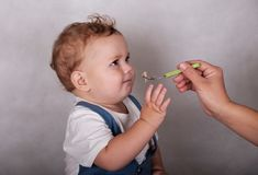 L'aspect européen de bébé mange du gruau d'une cuillère Photographie stock