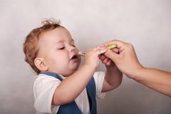 L'aspect européen de bébé mange du gruau d'une cuillère Photos libres de droits