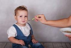 L'aspect européen de bébé mange du gruau d'une cuillère Photos stock