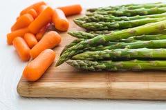 L'asperge et les carottes se ferment sur un hachoir en bois photos stock