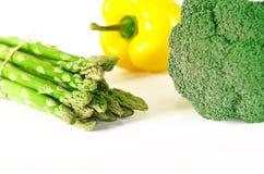 L'asperge, le rouge juteux et les poivrons oranges avec une queue verte se trouve à côté du paquet de laitue et le brocoli sont s photo libre de droits