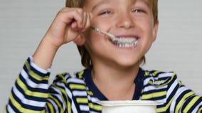 L'aspetto europeo del ragazzo sveglio è yogurt Ritratto di un bambino felice che si siede alla tavola Ecco, alimenti per bambini stock footage