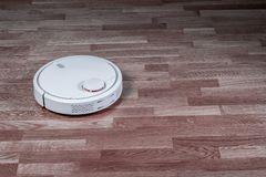 L'aspirapolvere robot bianco funziona sul pavimento laminato Robot controllato dai comandi di voce per pulizia diretta Astuto mod immagini stock