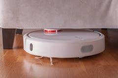 L'aspirapolvere robot funziona sotto il sofà nella sala sul pavimento laminato Il robot controllato dalla voce ordina per diriger Fotografie Stock Libere da Diritti