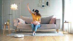 L'aspirateur robotique nettoie la salle avec une fille en VR-verres banque de vidéos