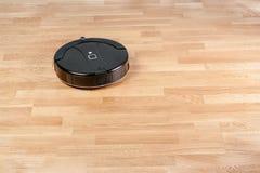 l'aspirateur robotique noir fonctionne sur les planchers en stratifié Ménage futé moderne de technologie de nettoyage Avec votre  image stock