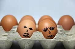 L'aspiration d'oeufs de Chicken's le visage de l'homme et de la femme a mis dans le plateau de papier d'oeufs Images libres de droits