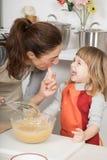 L'assaggio di risata del bambino e della madre ha montato la crema con il dito Fotografia Stock