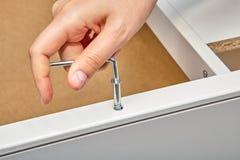 L'assemblatore della mobilia stringe la riparazione del bullone della camma in mobilia fotografia stock libera da diritti