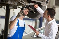 L'assesseur et l'homme de réparation examinent la voiture photo stock