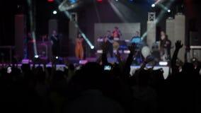 L'assistance heureuse Raisies de fond lent de vidéo animée remet le concert Hall Silhouettes Dancing People Raising de groupe de  banque de vidéos