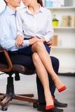 L'assistant de bureau s'assied sur le recouvrement de collègues photographie stock