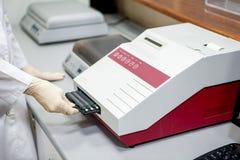 L'assistant de laboratoire charge des échantillons dans l'appareil pour l'analyse, plan rapproché photo libre de droits