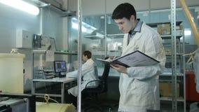 L'assistant de laboratoire concentré par jeunes fait des notes dans le dossier clips vidéos