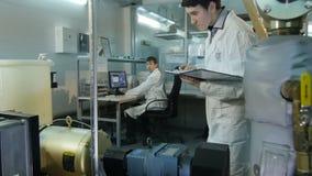 L'assistant de laboratoire regarde l'outil et le collègue à l'arrière-plan banque de vidéos