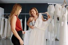 L'assistant de magasin aide la jeune mariée en choisissant le vêtement parfait Images stock
